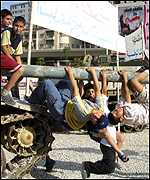 Lebanese boys play atop an Israeli tank on the first anniversary of Israeli troop pullout