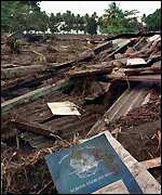 [ image: A schoolbook lies in the debris]