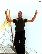 Mohammed Assadi, 25, flashes a victory sign after hoisting a Hezbollah flag.