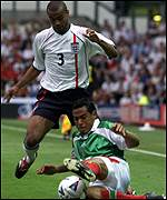 Ashley Cole is tackled by Mexico's Hugo Chavez