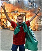 A Palestinian youth wearing a Hamas flag celebrates ithe Hadera bombing in front of a burning mock Israeli bus
