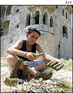 A boy plays with spent cartridges after an exchange of fire