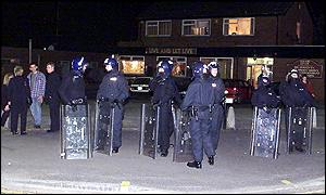 Police in riot gear stand monitor a tense Saturday night stand-off in Oldham