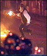 Rioter throws a petrol bomb