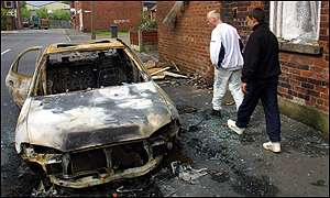 Two youths inspect a burnt-out car