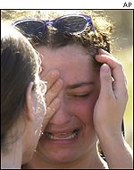 Two women cry during a funeral service