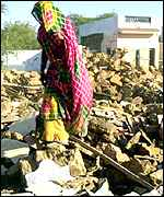 A woman picks her way over earthquake rubble in Gujarat