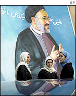 Women stand under poster of Iranian President Mohammad Khatami