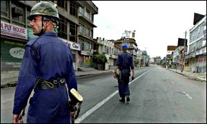 Police patrol the empty streets during the curfew