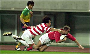 Wales' Adrian Durston dives in for his try despite Goshi Tachikawa's despairing tackle