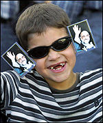 A young Iranian boy wearing a picture of President Mohammad Khatami  on his sunglasses
