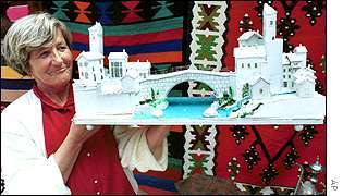 A Bosnian Muslim woman sells a model of the Mostar bridge