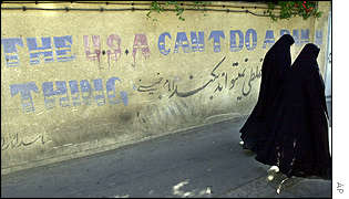Two women walk past a wall bearing an anti-American slogan near a polling station in northern Tehran