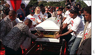 Pallbearers lower Nkosi's coffin into the grave