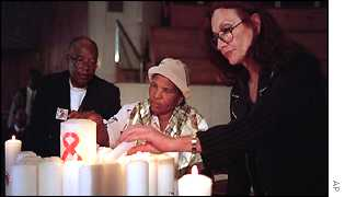 Nkosi's grandmother Ruth (centre) and foster mother, Gail Johnson (right) light candles