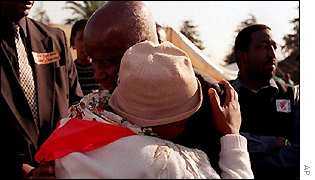 Nkosi's grandmother hugs Zambia's former president, Kenneth Kaunda, who attended the service