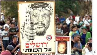 Jewish settlers hold up a poster Mr Arafat with a gun that reads 'Aiming at Jerusalem'