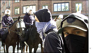 Mounted police and masked demonstrators