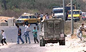 Palestinian children pelt an Israeli army jeep with stones