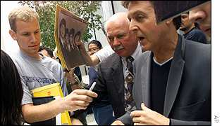 Paul McCartney, right, is surrounded by fans as he leaves the CNN studios in LA on 12 June