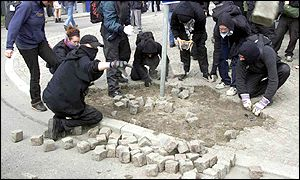 Demonstrators dismantle a cobblestone pavement