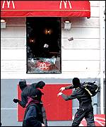 Masked rioters hurling rocks through the window of a McDonalds restaurant in Gothenburg