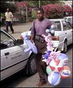 A Zimbabwean trader sells to a petrol queue in Harare