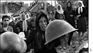 A survivor of the Sabra massacre holds up a helmet of a militia member she says was involved in the killings