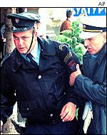 A Bosnian Serb police officer helps a colleague injured during demonstrations