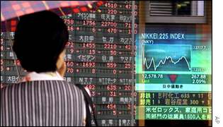 A woman checks share prices in a Tokyo window