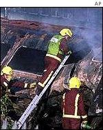 Firefighters attend to the smouldering wreck of one of the trains.