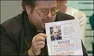 Tony Knox with 'Gerald Corbett: Wanted' poster at a news conference