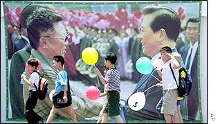Children walk past a poster showing the historic meeting of South Korean President Kim Dae-jung and North Korean leader Kim Jong Il