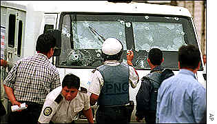 Police inspect an armoured vehicle riddled with bullets in Guatemala City