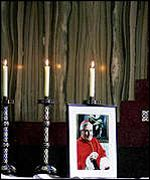 Candles burn beside a photo of Cardinal Winning