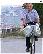 A Macedonian man riding a bicycle away from the village of Aracinovo