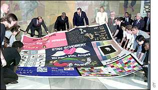 Activists hold a multi-coloured, patchwork quilt honouring millions of lives lost