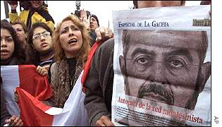 Opponents of Mr Montesinos hold Peruvian flags and a poster of Mr Montesinos in front of the National Police air base in Lima
