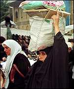 Iraqi women collects monthly food ration