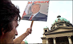 A supporter of Milosevic holds a picture of him during a rally outside the Yugoslav parliament building on Friday
