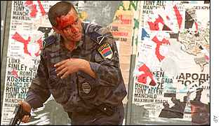 A Serbian policeman, who was beaten, pulls out his gun