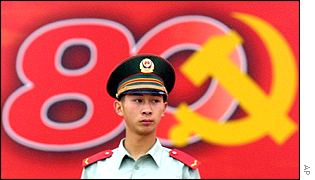A policeman stands beside a banner proclaiming 80 years of the Communist Party