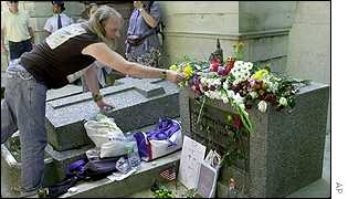 A fan of The Doors lead singer Jim Morrison, lays flowers on the rock stars grave at the Pere Lachaise cemetery, in Paris