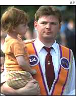 An Orangeman walks along with his baby daughter in his arms