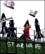 Protesters on top of a water tower, dressed as missiles and waving flags