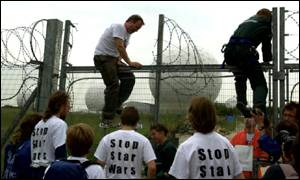 Greenpeace protesters scaling the fence and razor wire at Menwith Hill