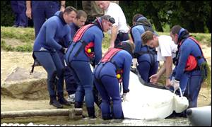 Gendarmes pull out a white stretcher from the Lac de Caniel