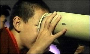 The Panchen Lama looks through a telescope as part of his trip