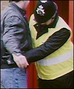 A police officer searches a man