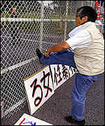 Japanese protester kicks the fence at Kadena Air Base